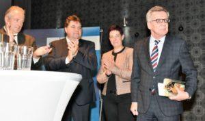 Minister de Maizière wird mit einem Präsent verabschiedet.