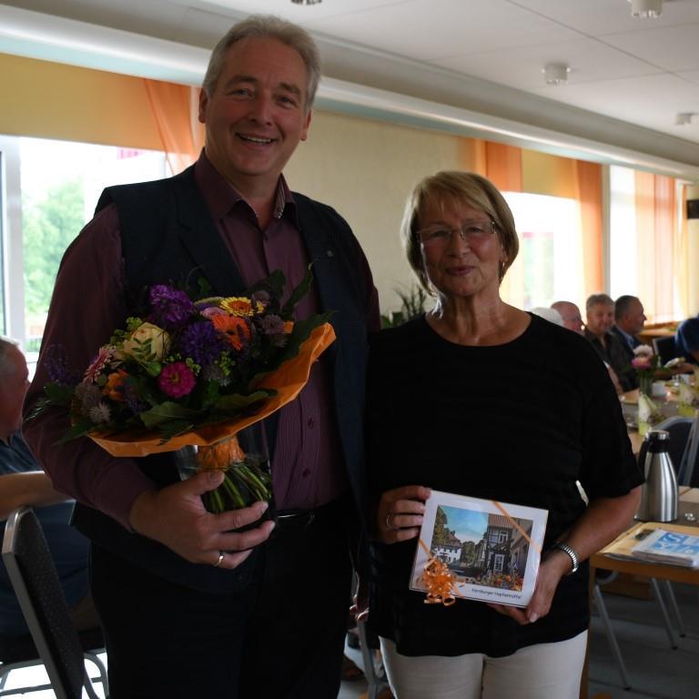 """CDU-Kreisverbandsvorsitzender Frank Oesterhelweg verabschiedet Elke Großer als Koordinatorin der """"Sozialen Sprechstunde"""" mit einem Blumenstrauß und Präsent."""