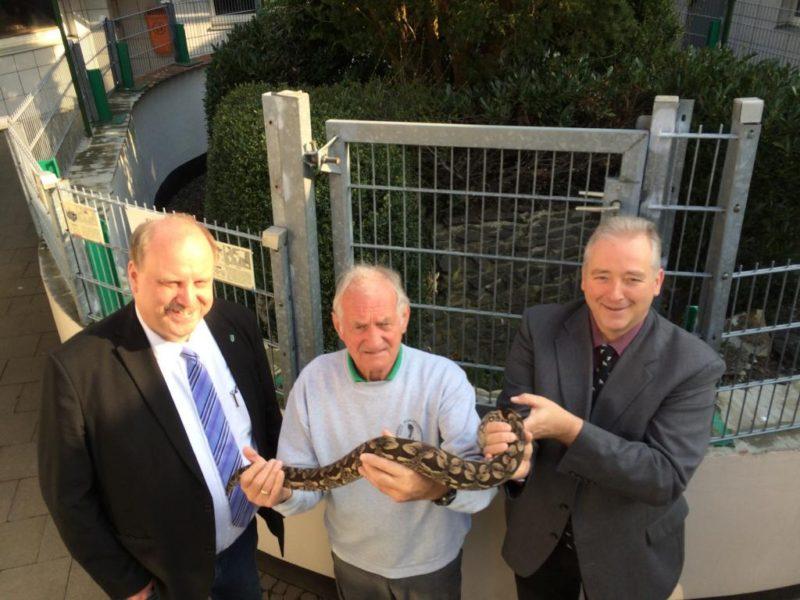Unser Bild zeigt Andreas Memmert, Jürgen Hergert mit einem seiner Tiere und Frank Oesterhelweg vor dem Terrarium, in dem die Besucher der Schlangenfarm in Deutschland heimische Schlangen beobachten können.
